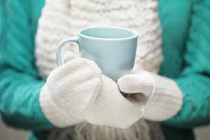 Frau hält Tasse mit Handschuhen